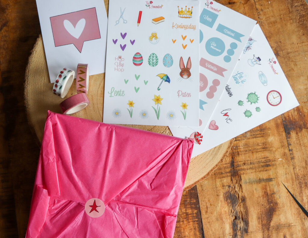 Een ingepakt roze cadeau, met daar boven stickervellen en drie rollen wasjitape